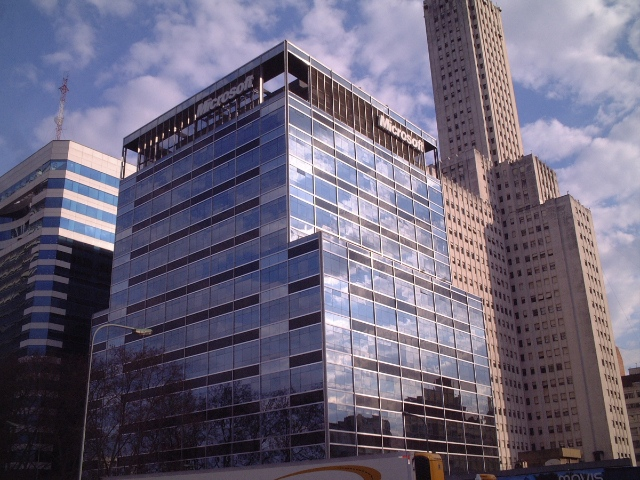 A tall glass building with the Microsoft logo at the top and a cloudy sky